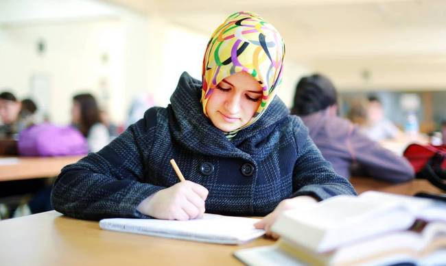 Muslim girl studying in library