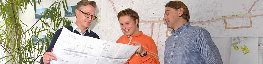Symbolbild: Bauplan und Mitarbeiter